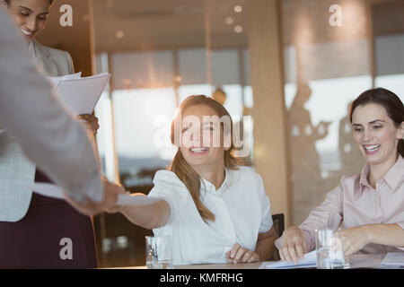 Smiling businesswoman handing paperwork to colleague in conference room meeting - Stock Photo