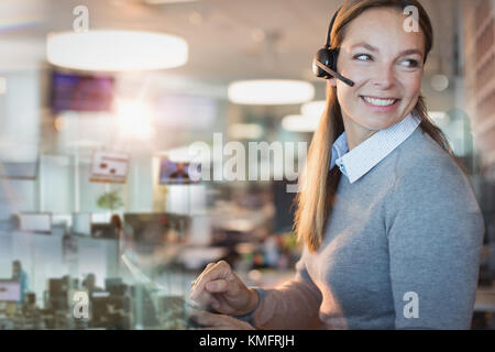 Smiling businesswoman with headset working in office - Stock Photo
