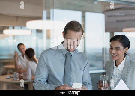 Businessman and businesswoman using cell phone in office - Stock Photo