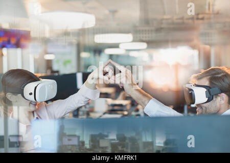 Computer programmers using virtual reality simulator glasses, touching fingers in office - Stock Photo