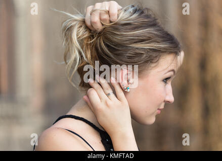 Side view of young attractive woman holding her hair in arms to show her earrings - Stock Photo
