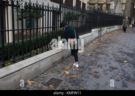 A lady stoops to tie loose laces on her trainers, in New Fetter Lane, on 27th November 2017, in the City of London, - Stock Photo