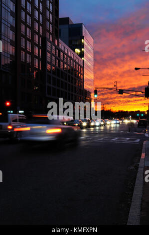 End of work day background. Night traffic and sunset sky at rush hour. Cars leaving city, scattered lights on office - Stock Photo