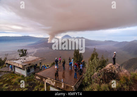 Tourists are enjoying the view during Bromo eruption from safe distance. - Stock Photo