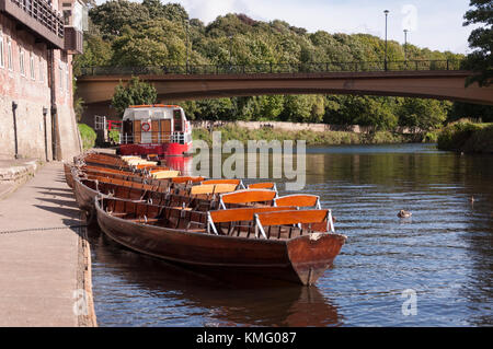 Pleasure cruiser, and rowing boats moored up on the bank side on the river Wear at Durham City in County Durham, - Stock Photo