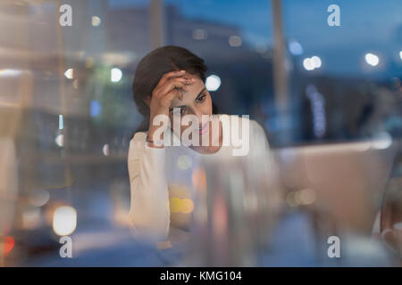 Tired businesswoman working late at laptop in office at night - Stock Photo