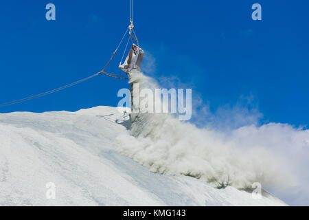 The bucket of the large quarry excavator is dumping waste products into the dumps - Stock Photo