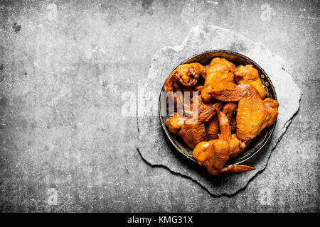 Smoked chicken wings. On a stone background. - Stock Photo