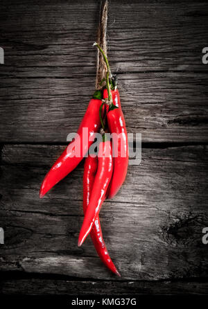 Red pepper on a cord. On a wooden background. - Stock Photo