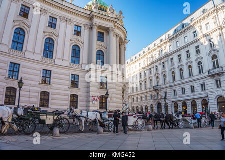 Horse-drawn carriage called fiaker is a differnet kind of taxi located at Hofburg palace in Michaelerplatz. - Stock Photo