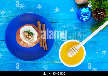 Baked apple stuffed with cottage cheese with cinnamon, walnuts, honey on a blue wooden background. A dietary dish. - Stock Photo
