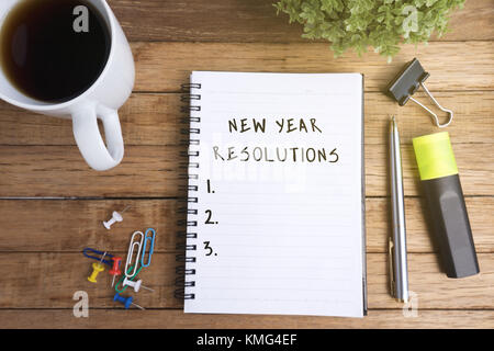 New Year Resolutions on Notepad with Cup of Coffee and Office Supplies. - Stock Photo