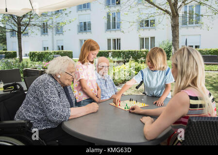 Multi-generation family playing board game at nursing home - Stock Photo