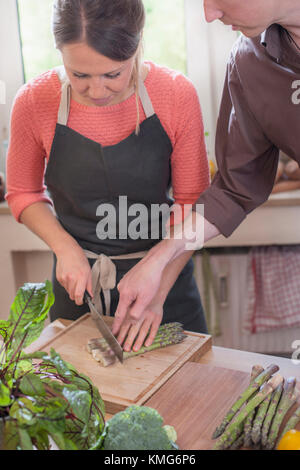 Couple cutting asparagus in kitchen - Stock Photo