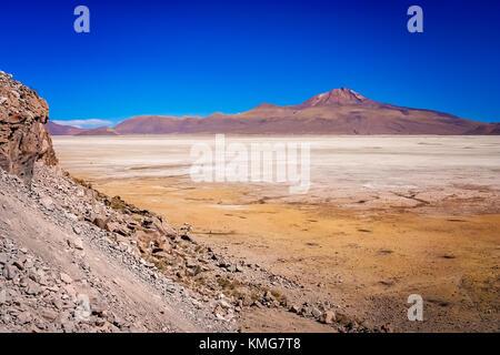 Dry land plain in the Altiplano mountains near Salar de Uyuni in summer, Andes, Bolivia - Stock Photo