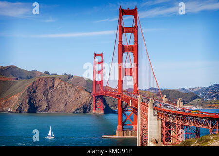 The Golden Gate Bridge, San Francisco, in late evening sun, with a sailing catamaran about to pass under into the - Stock Photo