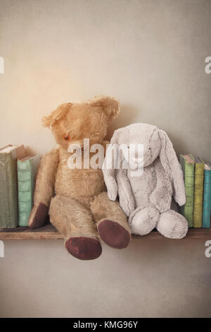 vintage toys on an old shelf with books - Stock Photo