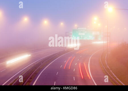 car traffic in a heavy fog in the morning, City expressway road, Lochkov tunnel, Prague, Czech republic - time exposure - Stock Photo
