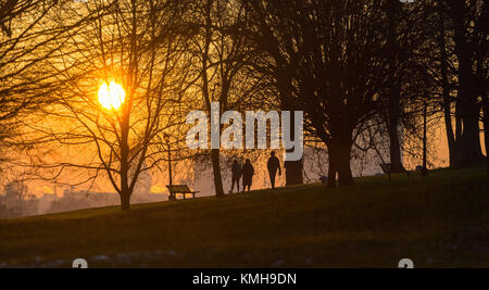 London, UK. 12th Dec, 2017. London, December 12 2017. Walkers on Primrose Hill as the sun rises on a clear very - Stock Photo