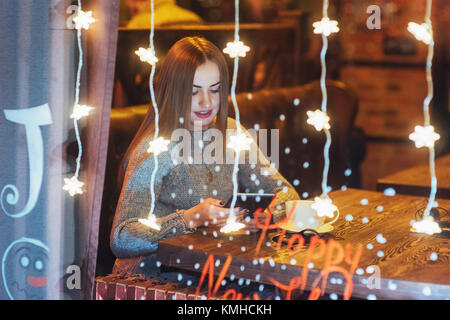 Young beautiful woman sitting in cafe, drinking coffee. Magic snowfall effect. Christmas, new year, Valentines day, - Stock Photo