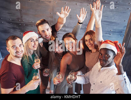 New Year is coming! Group of cheerful young multiethnic people in Santa hats on the party, posing emotional lifestyle - Stock Photo