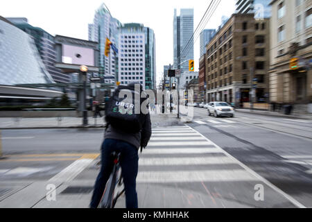 TORONTO, CANADA - DECEMBER 31, 2016: Uber Eats delivery man on a bicycle waiting to cross a street in the center - Stock Photo