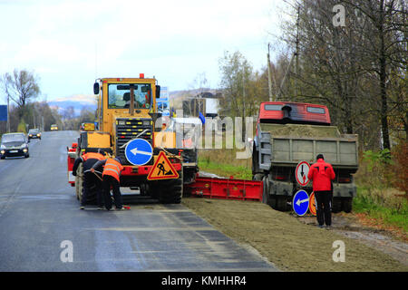 road-roller and repairmen make a repair of the asphalted road - Stock Photo