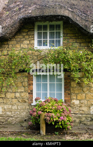 Detached house with a thatched roof and chimneys located just off the High Street, Towcester, UK - Stock Photo
