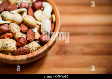 Assorted nuts in wooden bowl - Stock Photo