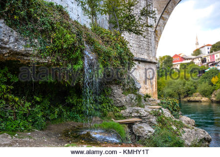 A small waterfall on the banks of the Neretva River under the Old Bridge in Mostar, Bosnia and Herzegovina - Stock Photo