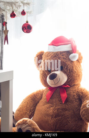 Teddy bear toy with Red Santa hat sitting under christmas tree ornaments - Stock Photo