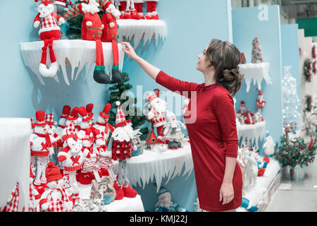 customer girl choosing gifts for Christmas and New Year - Stock Photo