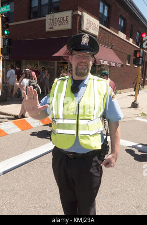 Policeman wearing a florescent safety vest directing traffic at Grand Old Day festivities. St Paul Minnesota MN - Stock Photo