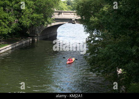 Young woman paddling her kayak in the channel from Lake Calhoun into Lake of the Isles. Minneapolis Minnesota MN - Stock Photo