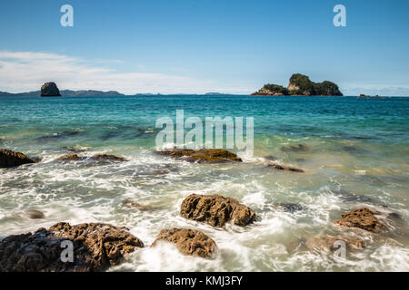 Waves of the Pacific Ocean break against jagged rocks on the shoreline of New Zealand. Off shore over the blue-green - Stock Photo