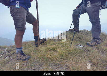Close-up of legs of young hikers walking on the country path. Young couple trail waking. Focus on hiking shoes - Stock Photo