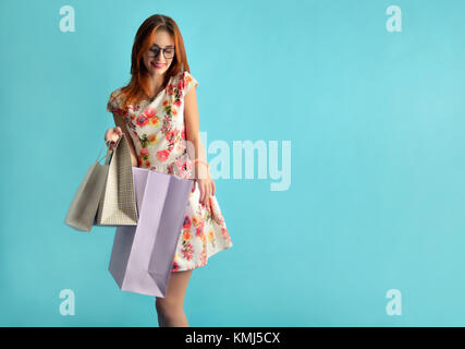 caucasian young female model in glasses in an white dress on the blue background. Girl holding in the hand a few - Stock Photo
