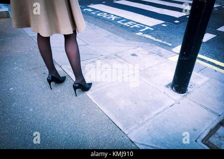 Close-up of the legs of a woman dressed in fashion with a coat, black stockings and high heels in the street beside - Stock Photo