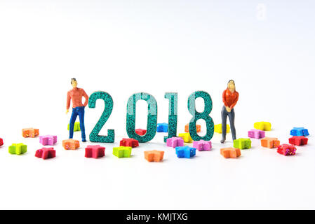 2018 New year concept man and woman miniature figures standing on 2 0 1 8 number with colorful stars on white background. - Stock Photo