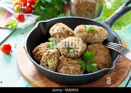 Homemade meatballs with buckwheat and egg stuffing. Cast-iron frying pan with delicious fried cutlets, fresh herbs - Stock Photo