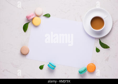 Colorful flat lay with flowers macaroons and cup of tea. Spring concept. - Stock Photo