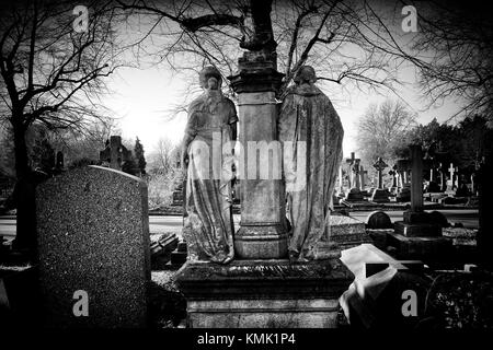 Rear view of two funerary sculptures in Brompton Cemetery, Fulham Road, London, England - Stock Photo