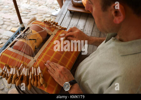 Man using bobbins for lace making, Le Puy-en Velay, Auvergne, Francestreet front - Stock Photo
