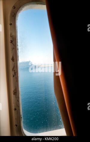 Sunrise seen from behind a ferry boat window. Mediterranean Coast, Palma, Majorca, Balearic Islands, Spain - Stock Photo