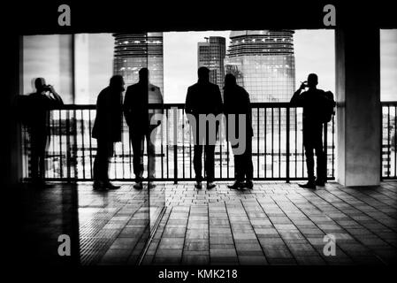 Silhouette of unrecognizable three man and reflected on a glass looking at the City from a balcony. Tate Modern, The City, Bankside, London, UK