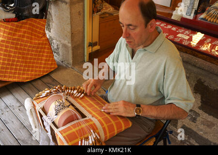 Man using bobbins for lace makingon sidewalk in front of store, Le Puy-en Velay, Auvergne, France - Stock Photo