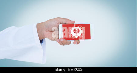 Male doctor holding smart phone with blank screen against digital composite of heart icon - Stock Photo
