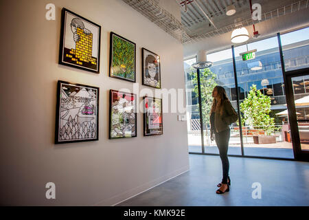 1e50fc54fe7 A young adult woman peruses the art collection of the Vans Shoe Company  corporate headquarters in