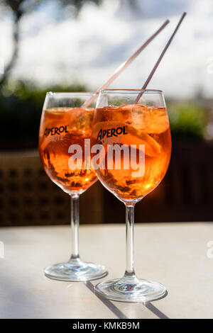 Two glasses of Aperol Spritz, a blend of Aperol, Prosecco and soda water with orange, on a table in an outside bar. - Stock Photo