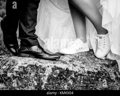 The bride wears sneakers for her wedding black and white - Stock Photo